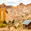 Remote cabin in an Oregon canyon with yellow fall trees and mountain cliffs