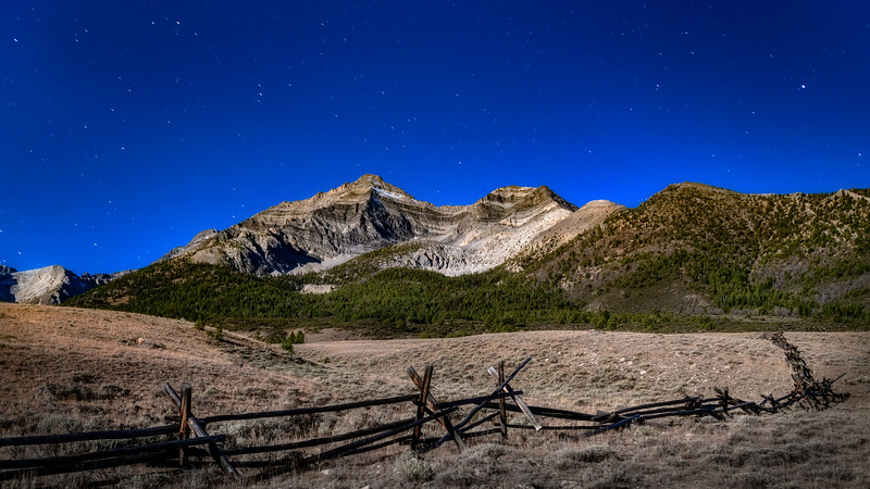 Mountain peak and fence by moonlight
