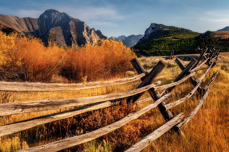 Rustic pole fence leads into the distant mountain range in autumn