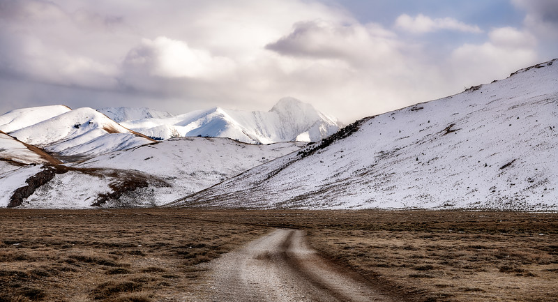 Gravel road leads into winter mountains in Idaho