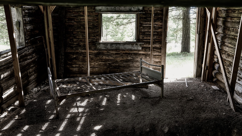 Old log cabin interior with a rusted spring bean on a dirt floor