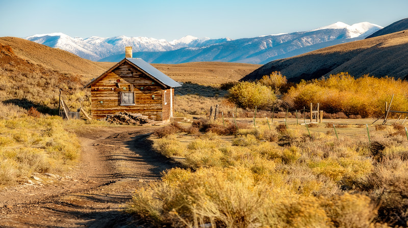 Mountain cabin with snow caped mountain range and fall bushes along a road