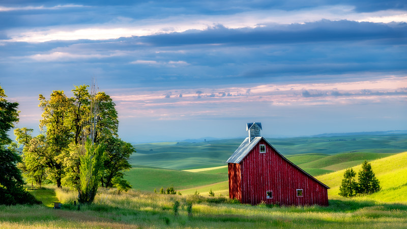 Red Barn with rolling hills of the Palouse in the light of morning