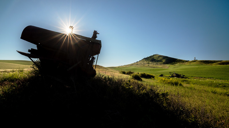 Old rusted combine and sunstar at Steptoe Butte