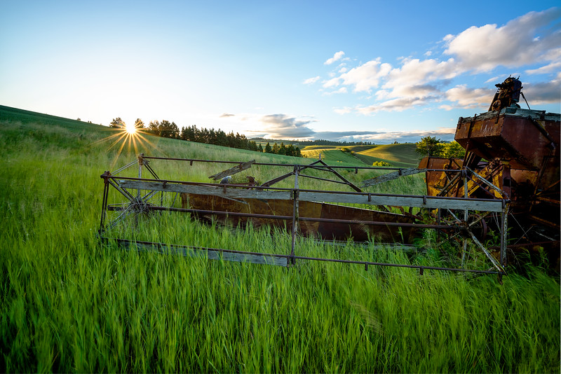Old combine in a field at sunrise