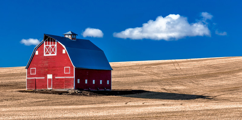 This old barn is located in Union Town Washington, which is just south of Pulman. It is right off of the highway. Hard to miss. Sometime the conditions are just right. I left Moscow to head back home after a visit with family and chose to drive on the Washington side. I stopped on the side of the highway mid-morning.  The sky was blue when I stopped, no clouds, but there were a few puffy clouds to the south. It appeared that they were drifting in the right direction. I felt a little silly standing on the side of a highway looking at a barn for must have been a half an hour. <br /> This image the result of waiting.  I liked the dark to light contrast the clouds help with, but also the color contrast between the blue sky and red barn.