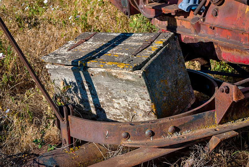 Abandoned on an old combine a wooden tool box is weathered
