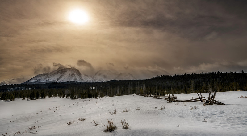 Afternoon sun shines of a snow field with Sawtooth Mountains