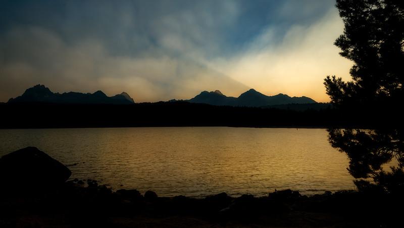 Last light of the day reflects through smoke onto Redfish Lake