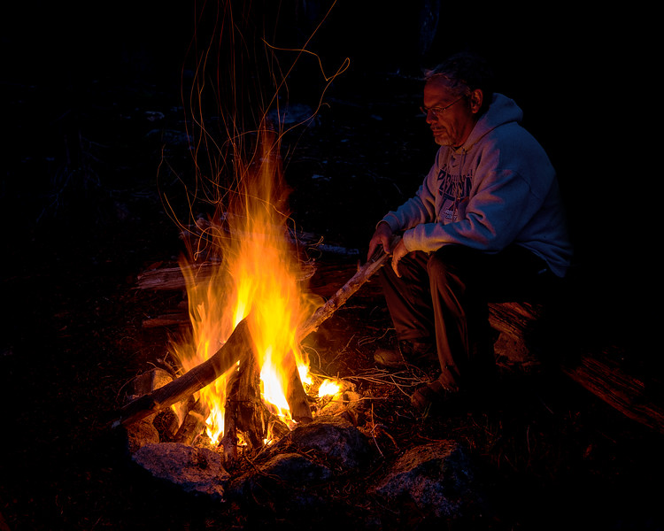 Glen Hush tends the fire on a cool crisp night
