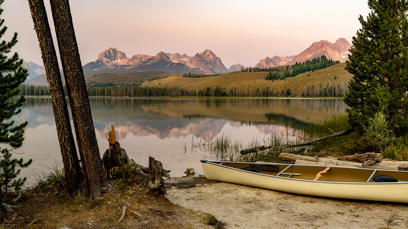 Canoe parked on the shore of an Idaho mountain lake at sunrise