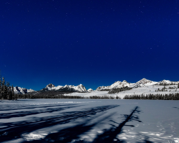 Long shadows from moon light point to the Sawtooth mountains at Little Redfish Lake