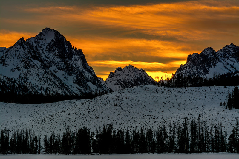 Warm yellow light fades over the Sawtooth mountains of Idaho as the sun sets on a cold winter night