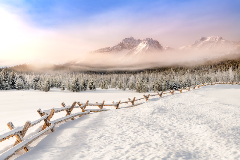 Round pole fence leads through a snow field towards the Sawtooth Mountains