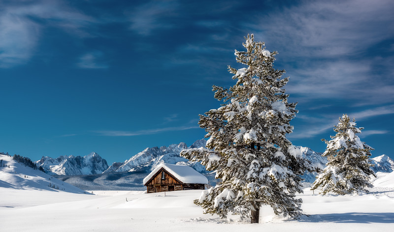 Winter cabin with Sawtooths backdrop in winter
