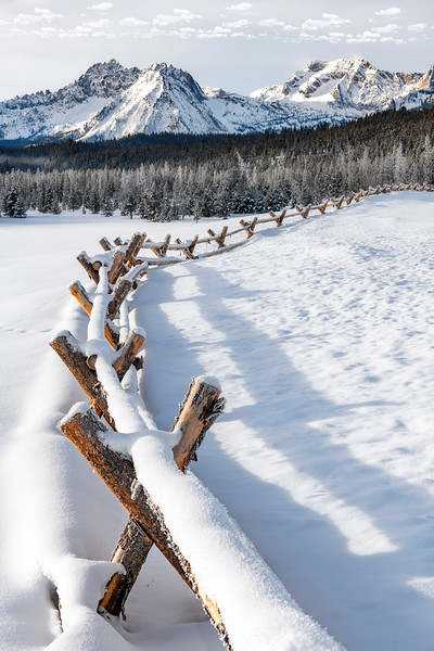 Pole fence leads deep into the Sawtooth Range winter