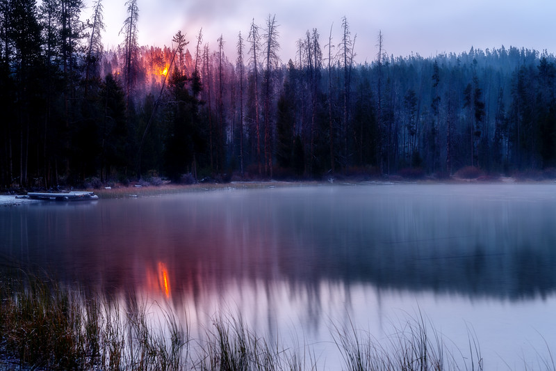 Forest fire burns in the woods above a beautiful mountain lake