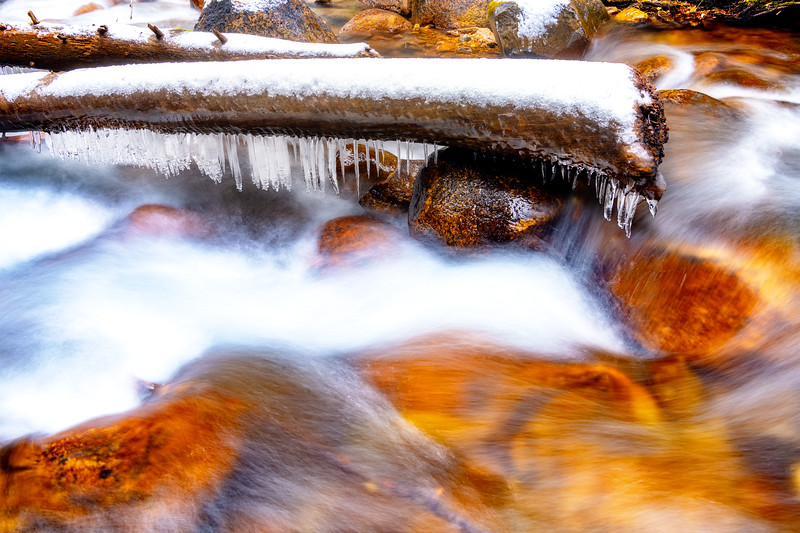 Snow covered icy log in the middle of a wild river flowing over rocks