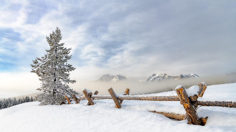 Fence leads to the Sawtooth Mountain of Idaho in the winter