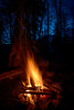 Campfire and sparks against blue sky of night