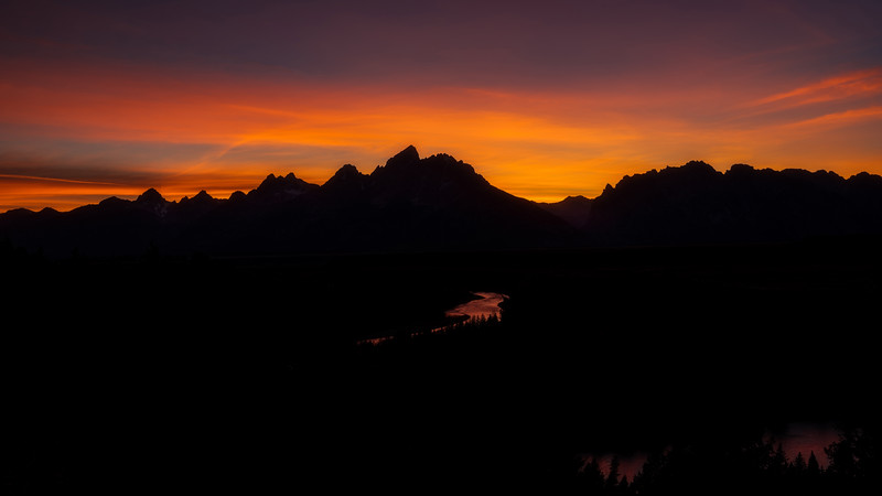 Sunset reflects in the Snake river as it winds to the Tetons