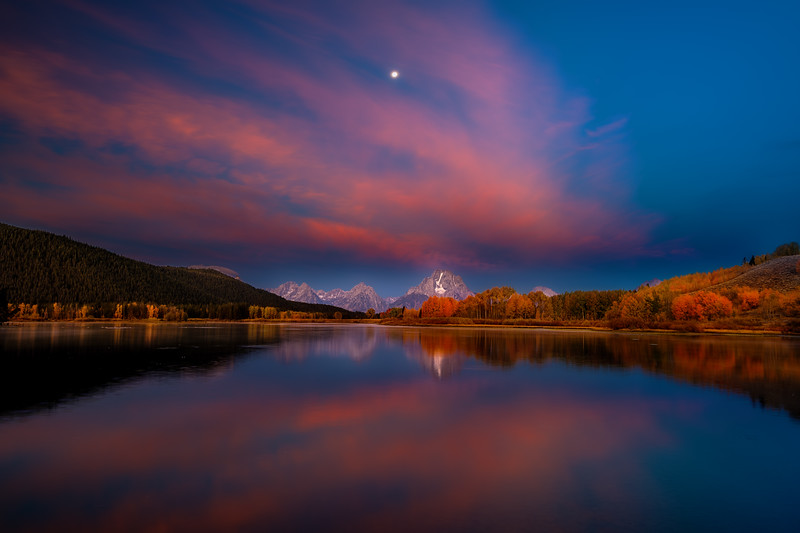 Warm colors of morning reflect in the Snake River at Oxbow
