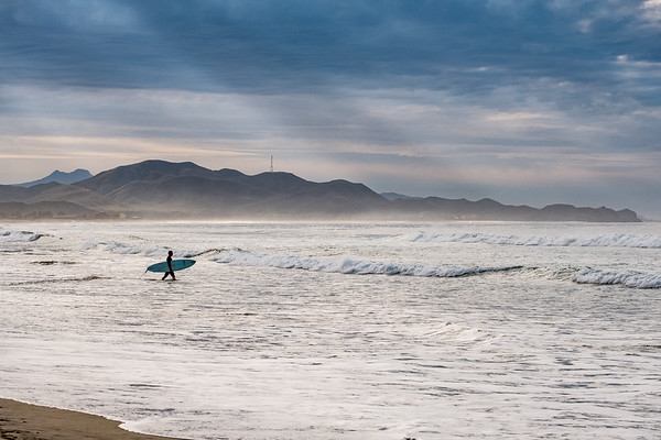 A lone surfer heads out to catch the waves at Cerritos.