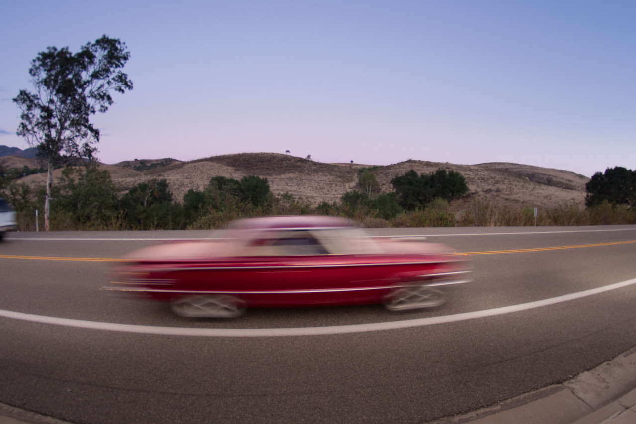 A red classic car blurs past us into the twilight.