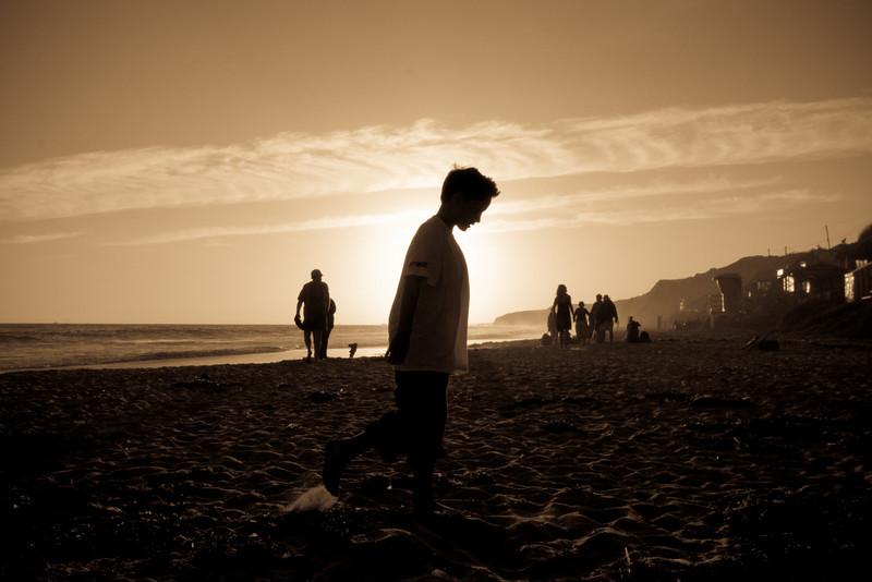 Boy Walking in Front of Sun