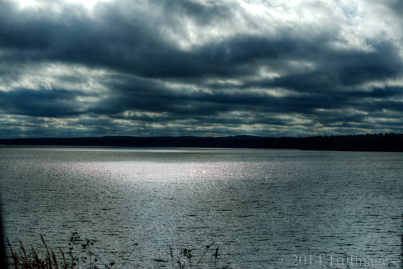 Jan 7<br /> Angry skies<br /> <br /> The sun finally peeked through these menancing clouds creating a pool of light on the lake.
