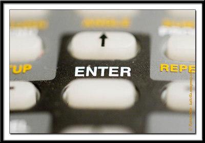 """TV remote, focused on """"T""""."""
