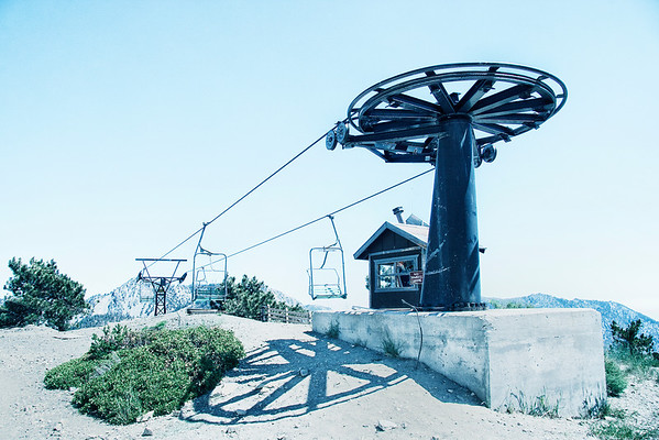 The wheeled turnstile tower rises monolithically above the lilliputian structure at its base. A shadow of the spoked mechanism paints the ground below. The lift and its origins.