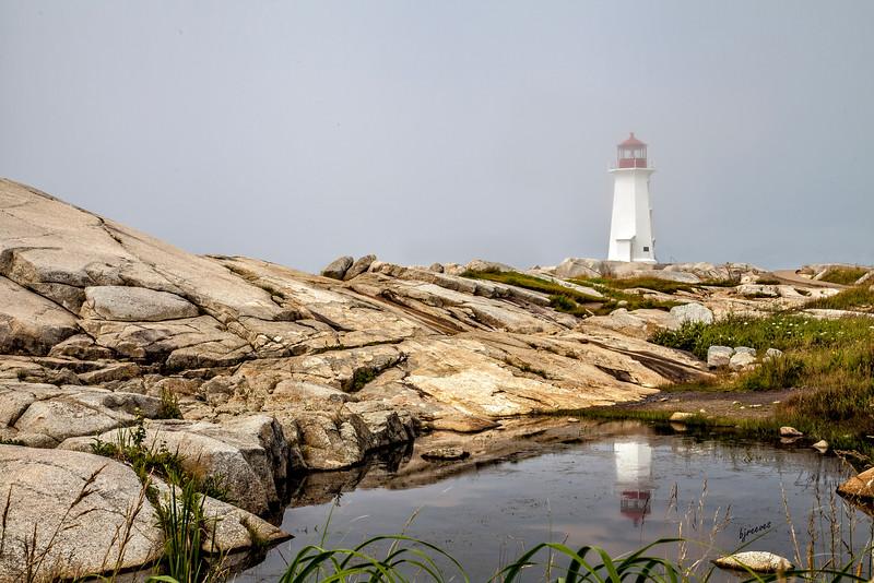 Peggy's Cove Lighthouse as the fog rolls in. Nova Scotia, Canada
