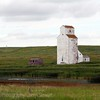 This grain elevator sits in a pasture, no road, or tracks, or other buildings. Rural Saskatchewan Canada.