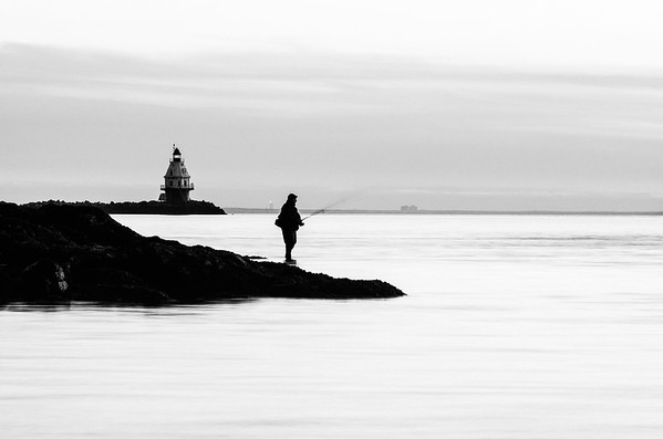 A man is seen fishing off of  a rock near LIghthouse Point Park in New Haven, CT