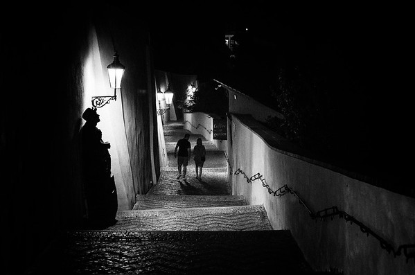 A couple walks down the steps from Prague Castle