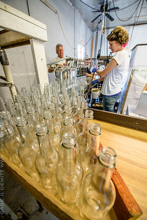 friends get together on the bottling line to manually fill, cap, and monitor quality control