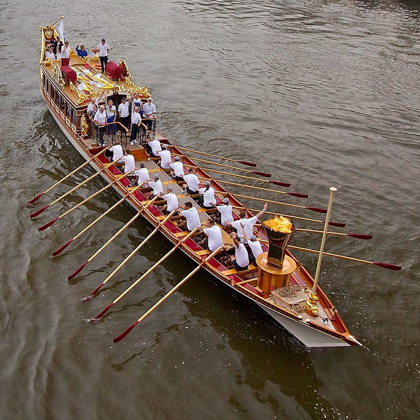 The Olympic Flame is rowed down the Thames on Gloriana on the morning of the London 2012 Olympic Opening Ceremony.