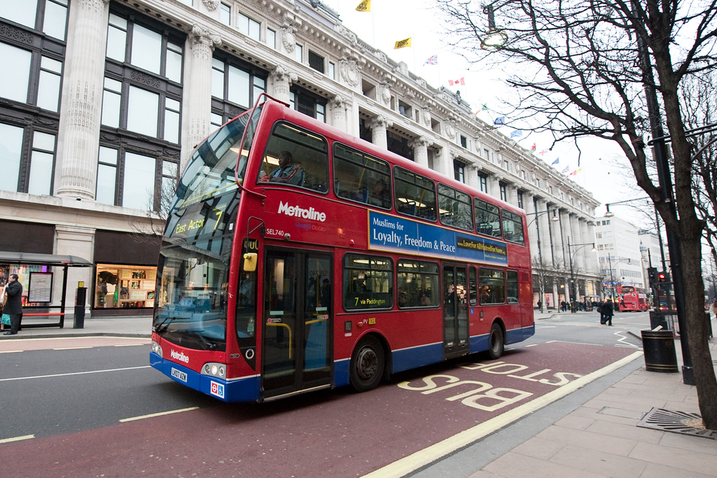 London Transport Bus in Oxford Street in front of Selfridges with AMA UK peace message.