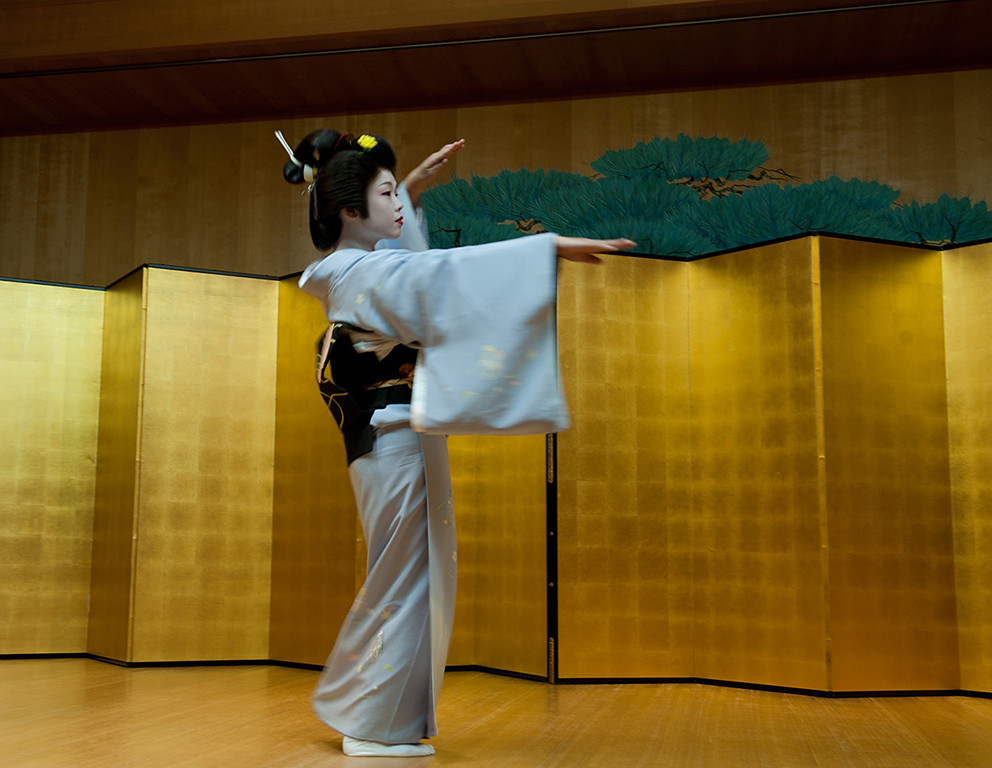Geisha dancing at a performance in a theatre.