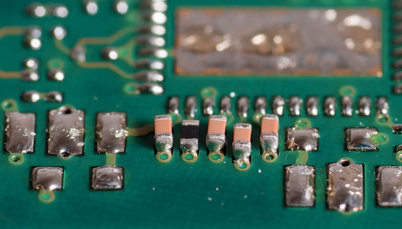 Five components on a printed circuit board. The tan colored components are capacitors and the black component is a resistor. Each component is roughly 1mm x 0.5mm. This board was run as a test to evaluate the quality of solder joints on these components (thus none of the surrounding components are placed).<br /> <br /> Lighting setup is a SB-600 triggered remotely shooting through sheet of copier paper.