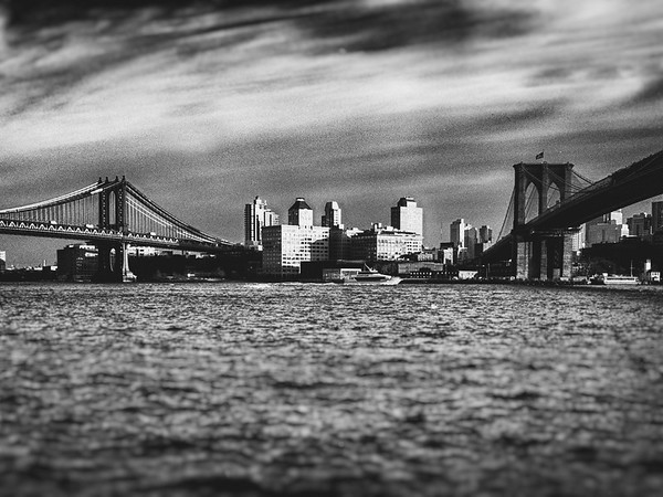 <h2>Brooklyn Bridge and Manhattan Bridge - Two Bridges - New York City</h2> - By Vivienne Gucwa  The light after a storm in New York City has its own charm. The rivers calm down from their frenzied co-mingling with the rain and the sun comes out to paint the bridges and skylines in light. And if you are there for the exact moment that all of these elements occur, it's nothing short of incredible.   ---  I like to wait a few months sometimes before I contemplate certain scenes that I have photographed. The distance between the experience and the nostalgia for the initial experience seems to add a certain complexity to the memory. This particular view was captured with the Sony A99 on an absolutely frigid day back in February shortly after a storm passed through. The river was so choppy that waves were literally slapping up against the edge of where I was standing and splashing onto the concrete. I had never seen the light illuminate the Manhattan Bridge, Brooklyn Bridge, and Brooklyn skyline in such a spectacular way before though.   I would stand there again a thousand times enduring the river's icy advances just to get a glimpse of this light.   ---