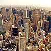 <h2>New York City</h2> - By Vivienne Gucwa  Growing up in Queens, a borough of New York City, I was surrounded by a general attitude of contempt and disgust regarding anything tourist related. My father who worked nights as a newspaper pressman in Manhattan hated going into Manhattan for anything other than work (his job was back-breaking) and my mother echoed the same jaded sentiment towards 'touristy things' in Manhattan as her other outer-borough friends. The 'city' (as many people still call it) was something to be proud to live in very close proximity to but anything too popular in the 'city' was the subject of eye-rolls.  I grew up mimicking this sentiment; a sort of 'been there, done that' mentality. We would only ever go to things like Times Square and the Empire State Building when relatives or friends visited and there was a silent stoicism related to showing 'the sights' to 'out-of-towners'. I always found this amusing. These sights that were derided as nothing more than trite spectacles were the same sights that my parents deemed worthy to spend time taking people to when people came to visit us.  When I moved to Manhattan a decade ago, I carried this attitude with me. It wasn't until I started taking photos that I fully opened my eyes (so to speak). Granted, I had always found beauty in the things many people passed over; architectural details on tops of buildings, the way that sunlight hit buildings at different times of the day. However, when I finally discarded the jadedness that permeated my early years I started realizing how utterly phenomenal and fascinating all those 'touristy' things are.  It may have taken me many years to fully grasp why people come from all over the world to gaze lovingly at sights and architectural marvels like the Chrysler Building and the Empire State Building but now that I know it's hard not to gaze at these sights with anything but wonder. There is so much to be in awe of in this spectacular city.  ---  This is an early morning view from the top of the Empire State Building looking out over the huge variety of skyscrapers that populate the skyline of midtown.   In the distance sits Central Park with the MetLife Building and Chrysler Building to the right and Bryant Park and Rockefeller Center towards the left and center. The Ed Koch Queensboro Bridge is to the right of the Chrysler Building in this view and Queens can be seen to the right of the bridge disappearing into the haze.  ---