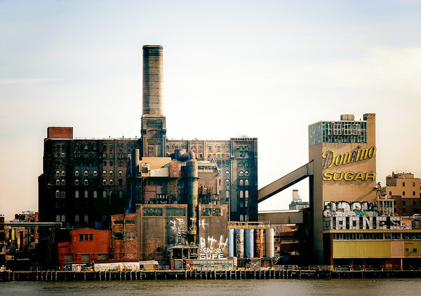 <h2>Oxidation - Domino Sugar Factory - New York City</h2><br><br> - By Vivienne Gucwa<br><br>  There is something remarkably touching about urban decay. It is as if sorrow and longing can be traced in the peeling layers and crumbling brick. In warm sunlight, the rich colors created by iron oxidation produce the most beautiful textures on old pipes and metal framework. The memory of those who graced the intricate insides of these structures is delicately preserved by the faded remnants that remain.<br><br>  During the period following the Civil War, New York was the top provider of refined sugar to the United States, and for a period of time the Domino Sugar factory in Williamsburg, Brooklyn was the largest sugar refinery in the world. At one time, the factory employed over 4,000 workers and processed 3 million pounds of sugar a day.<br><br>  After nearly 150 years of service, the factory shut down in 2004 due to a decline in demand. There is a new plan for this space to make it a residential space which is being actively protested by groups like the Waterfront Preservation Alliance and the Landmarks Conservancy who believe that huge development in this space would destroy the history and architectural legacy of the sugar factory. I am inclined to agree with their assessment.<br><br>  ---