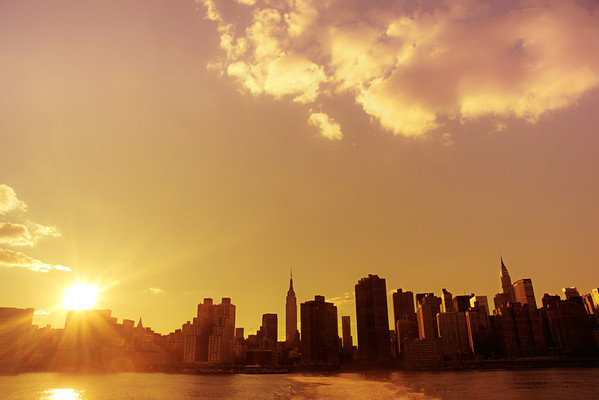 <h2>Skyline Sunset - New York City</h2> - By Vivienne Gucwa  Late summer and early autumn sunsets in New York City are intensely beautiful. The city seems to cling to every bit of sunlight through a haze that sleepily hangs low over the urban waterfront. This was taken near the end of a four hour long ferry ride back and forth around the East River in the late summer. There were barely any people on the ferry that day and I spent entire rides just taking note of the sun's descent in the sky.   When this moment occurred, it was so brief and fleeting and yet so dramatic in its intensity as the sun dipped towards the midtown skyline grazing the skyscrapers that I barely even knew if I captured it properly since the waves were kicking up in the river and the boat was swaying up and down over the waves. By then, I had gotten my 'sea legs' and knew the exact way to stand and counter the movement with my camera in my hands.   And the sun-kissed skyline drifted away from view and descended into the twilight of evening.  ---   This view is of the New York City skyline in midtown including the Empire State Building and the Chrysler Building during the last moments of a sunset as seen from the East River.   ---