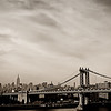 "<h2>The Manhattan Bridge and New York City Skyline</h2> - By Vivienne Gucwa   ""Chapter one. ""    ""He adored New York City.  He idolised it all out of proportion. ""                        Uh, no. Make that ""He romanticised it all out of proportion. ""                        ""To him,  no matter what the season was,                         this was still a town that existed in black and white                        and pulsated to the great tunes of George Gershwin. ""  If there is one opening sequence in cinema that perfectly illustrates even a tiny iota of the overwhelming love I have for New York City, it's the opening sequence to Woody Allen's Manhattan which is where the dialogue quoted above originates. I know that people have very definite ideas about Woody Allen but his early body of work still contains some of my favorite interpretations of life in Manhattan and this particular opening still chokes me up absolutely every time I watch it  especially the montage from 1:52 on. I actually learned how to play Gershwin's Rhapsody in Blue on the piano when I was younger almost entirely because of this opening sequence.  I was asked a while ago if I ever get bored or jaded about certain views or landscapes in New York City. I didn't really know how to answer the question without sounding like a blubbering idiot. I know many people seem to get bored of overly-photographed parts of New York City but for me, there is always something new and something special imparted to these landscapes based on each individual artist's perspective.   The photo in this post is of a landscape that overwhelms me every time I lay eyes on it.  For me, this scene encompasses a feeling that is hard to express entirely in words. It's how the light falls onto the Manhattan Bridge embracing its architecture in a glow while the skyline gracefully pushes through the dreamy haze distilling the essence of New York City down to its purest forms of hope, beauty and possibility.   ---"