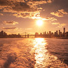 <h2>The New York City Skyline at Sunset</h2> - By Vivienne Gucwa  Late summer sunsets over New York City are the most intoxicating.  The bubbles from the wake of boats in the river go right to the head.  And the sun's trail of gold kisses on the water  lead straight to the heart of the city.  ---  It's this time of year when I start to miss late summer sunsets like this in New York City. When I need to clear my mind, I head to the water. Sometimes I go to the beach to listen to the waves and sometimes I go to the river to gain perspective on everything going on in my life. I don't know what I would do if I lived in a land-locked area.  On the day that I took this photo, I rode the East River Ferry for 4 hours straight (the day-pass is incredible) watching the light stretch across the sky and cityscape changing subtly every hour until the sun burst over the city like a supernova. The waves were perfect that day. The East River Ferry stops in both Manhattan and Brooklyn going from 34th Street in midtown, down to Wall Street's Pier 11, passing under each of lower Manhattan's bridges and then across to stops in Brooklyn and Queens connecting at piers in DUMBO, Greenpoint, Williamsburg and Long Island City.  ---