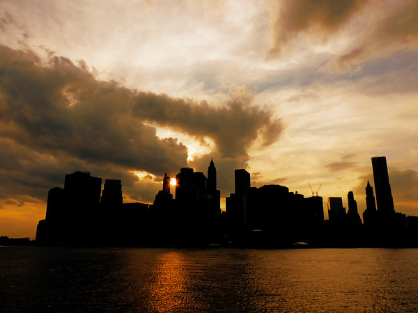 <h2>Sun Fire - The New York City Sunline in Silhouette at Sunset</h2> - By Vivienne Gucwa  I used to refer to sunsets as sunfire.  Those first sunsets burned through my retinas into the innermost recesses of my mind.  Clouds poured over the smoldering sparks of orange like thick plumes of smoke and before the sun extinguished itself, it burned the brightest of any flame in existence.  When the sun sets over New York City, it's as if a thousand flames dance across the sky, leaving embers scattered across the skyline in the wake of it's burning: like a fevered dream scattering its remnants across the mind before the deepest of slumbers.  I used to refer to sunsets as sunfire.  I still do.  ---