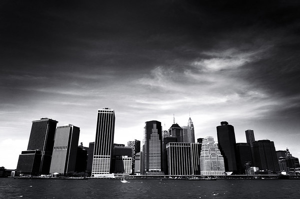 <h2>New York City Skyline</h2> - By Vivienne Gucwa  It's in the way the city rises   up towards the sky  conducting the clouds and waves  like a symphony.   The crescendos are the  loud heartbeats   of lovers and dreamers.  And the diminuendos are the  whispers of hope  uttered on soft breaths  infused by the promise of  something greater.  ---  This view is of the iconic skyline of Lower Manhattan. It features the skyscrapers of the Financial District. It's the view you see when you are heading towards or away from Manhattan by boat. It's a study of lines and shapes and it never fails to take my breath away.   ---