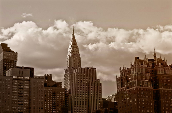 <h2>The Chrysler Building and New York City Skyline </h2> - By Vivienne Gucwa  This is a favorite view of the Chrysler Building. In truth, the Chrysler Building is my favorite skyscraper in New York City. I have always loved the art-deco architecture of it's spire and how its needle pokes out above the other skyscrapers that populate the New York City skyline in midtown Manhattan.   This view is looking west towards Manhattan and sitting in the foreground are the skyscrapers of Tudor City: neo-gothic historic buildings that lay their claim to fame for being part of the first residential skyscraper complex in the entire world.   ---